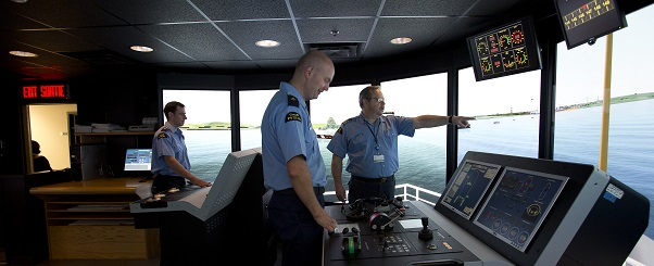 Two officer cadets receiving instruction in a marine navigation simulator