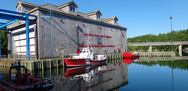 Training vessels sit on calm water next to the boat shed