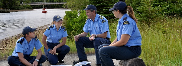 Three officer cadets chat with an instructor next to the water
